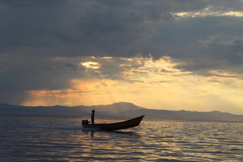 man in brown boat on sea during sunset