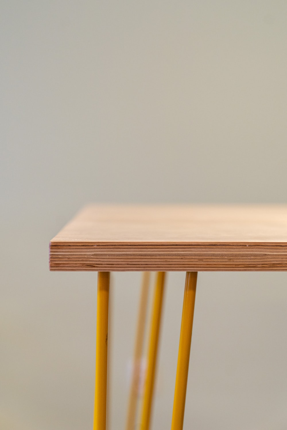 brown wooden table with yellow steel frame