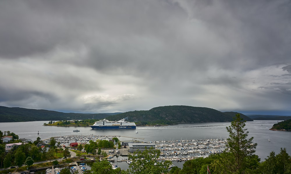 white boat on body of water near green mountain under gray sky