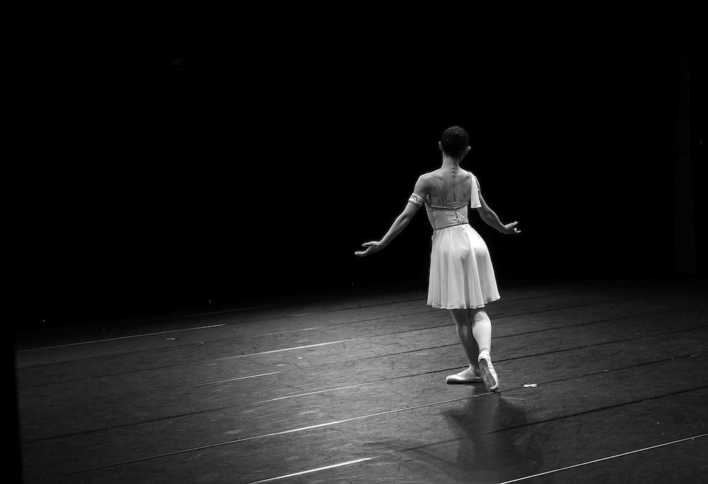 woman in white dress walking on black floor