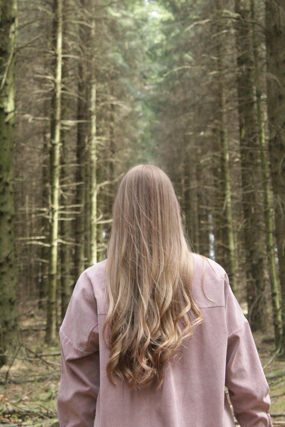 woman in brown hoodie standing in forest during daytime