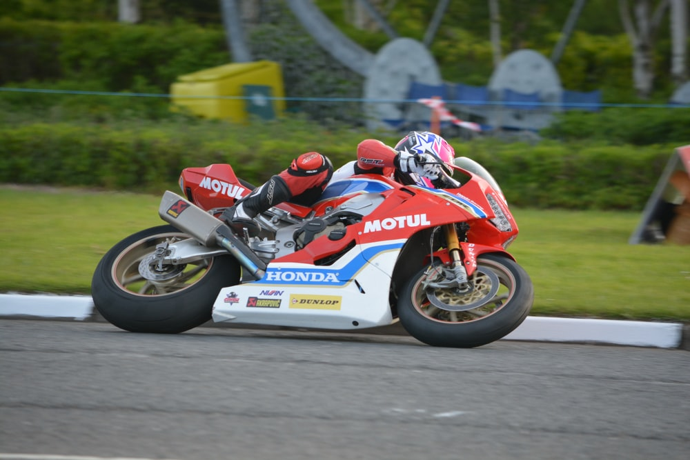 man in red and white racing suit riding on white and blue sports bike
