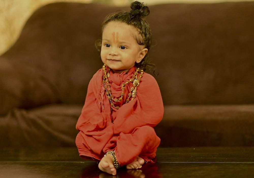 girl in red long sleeve dress sitting on brown wooden floor