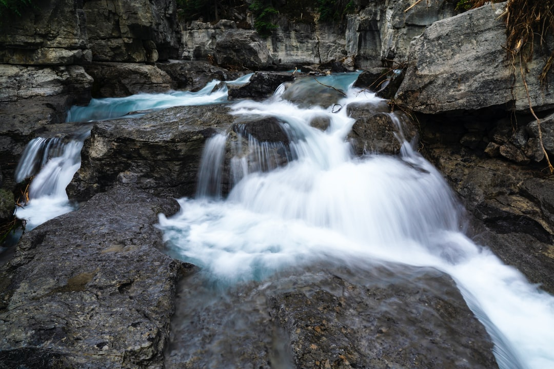 Fresh Spring Water Flowing Down Rocks With White Waterfalls Slow Shutter
