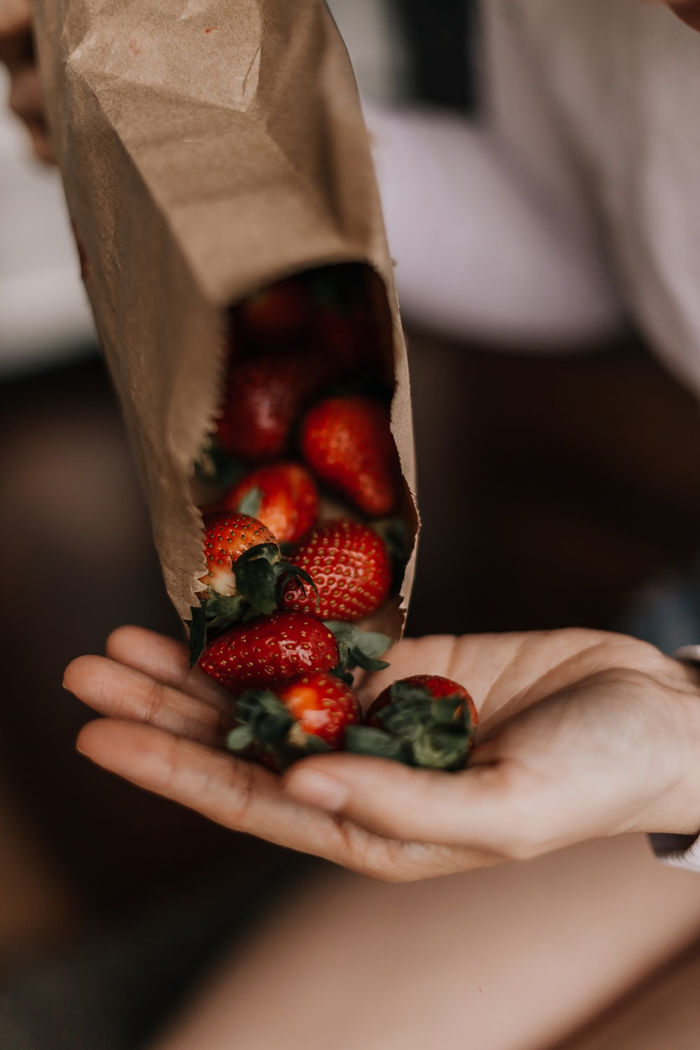 person holding red and green fruits