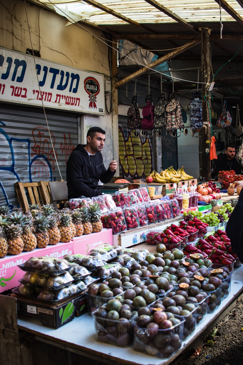 man in black long sleeve shirt standing in front of fruit stand