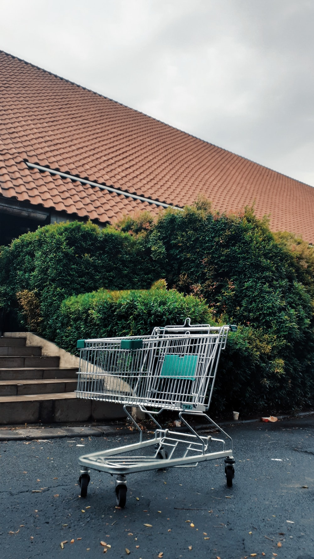 green shopping cart on gray concrete stairs