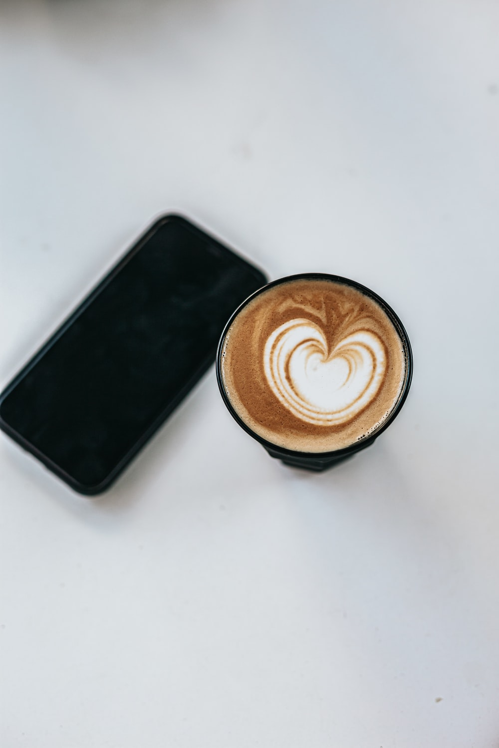 black android smartphone beside brown and white ceramic mug with coffee