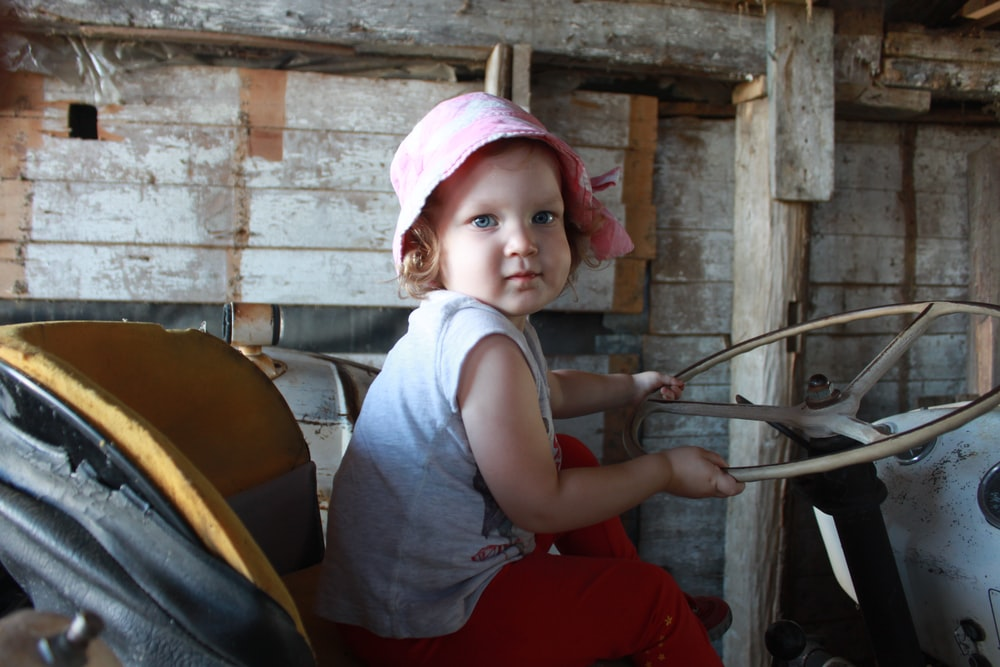 girl in gray tank top and pink bucket hat sitting on chair