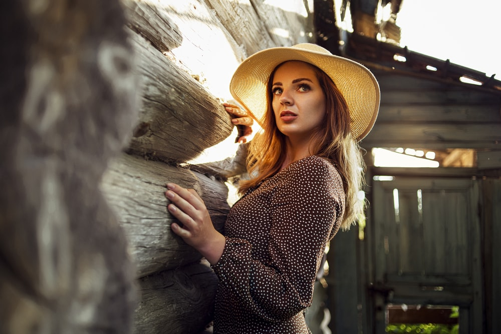 woman in black and white polka dot long sleeve shirt wearing brown hat