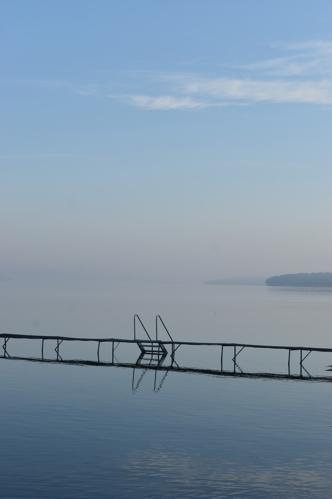 The water is calm near the boat dock as behind a haze sets over the lake