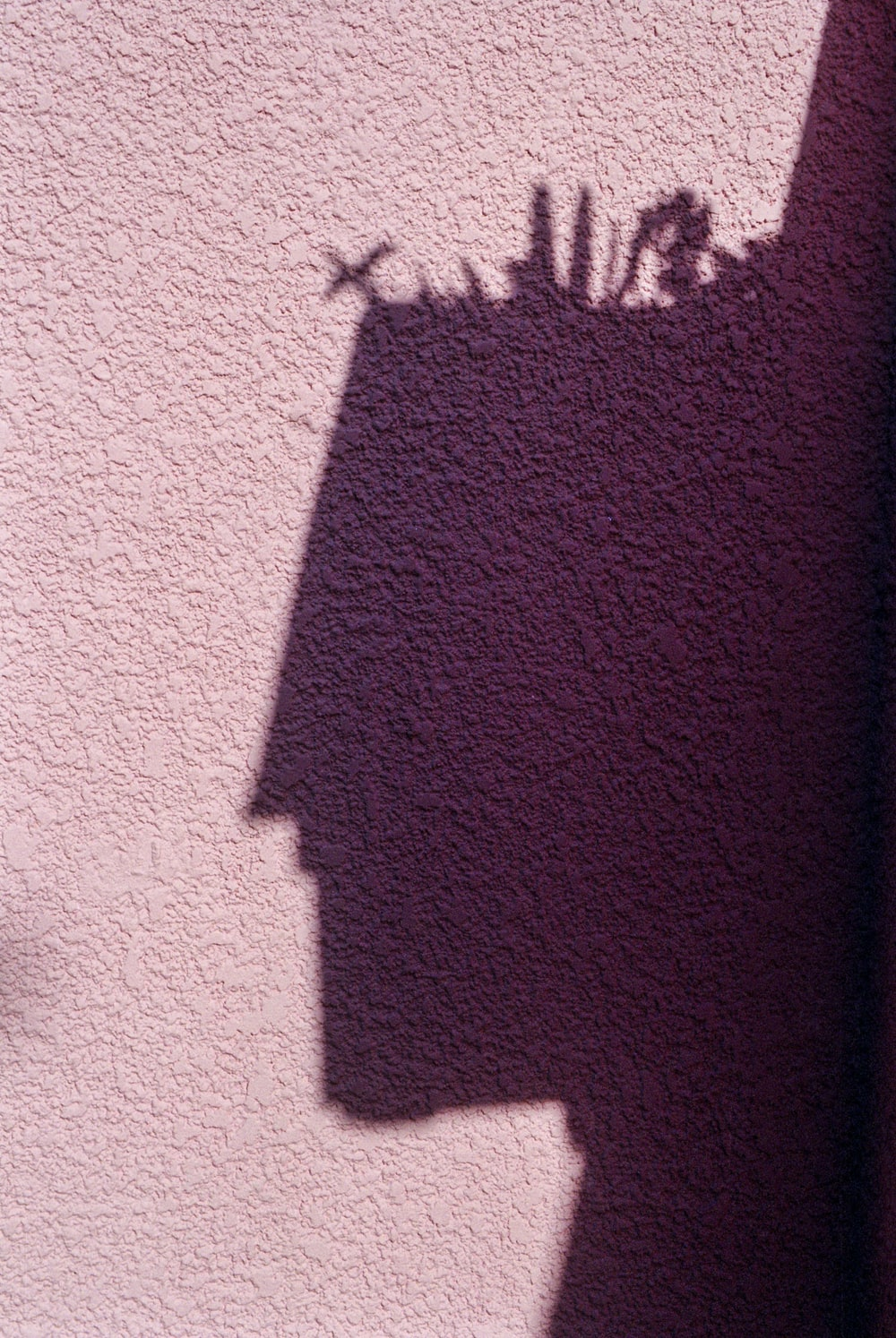 shadow of person on red concrete wall