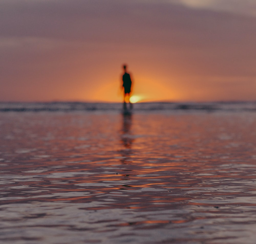 person standing on sea water during sunset