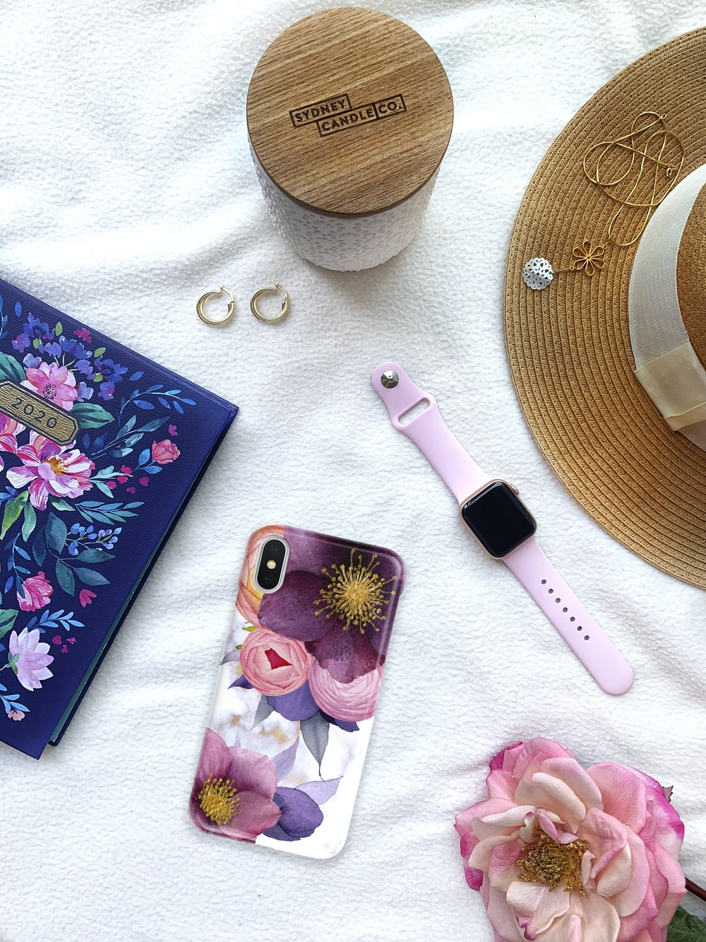 pink and black hair brush beside purple and white floral iphone case