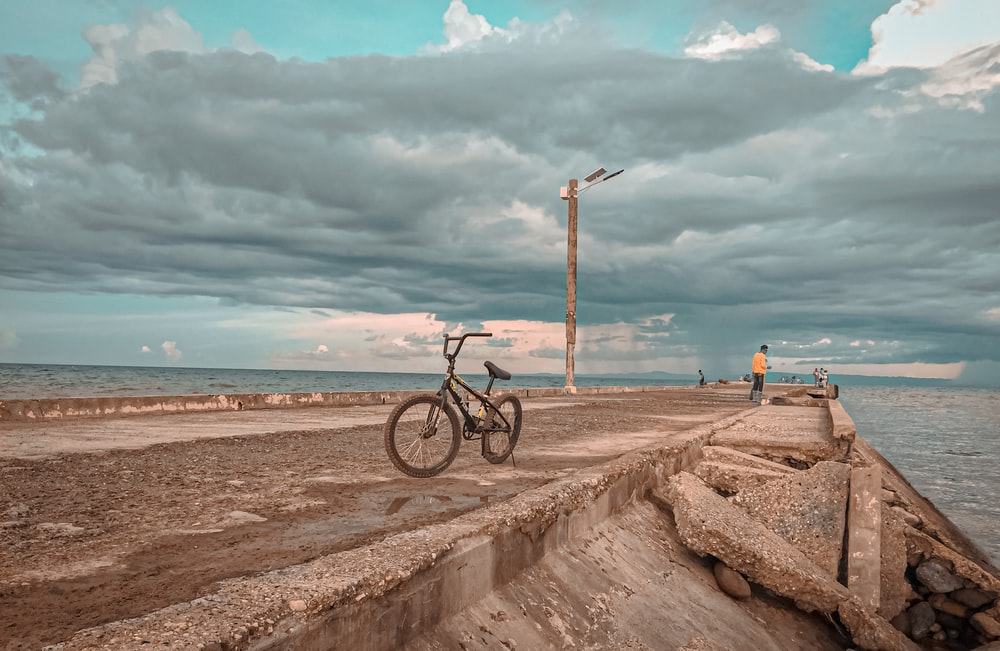 black bicycle on brown sand near body of water during daytime