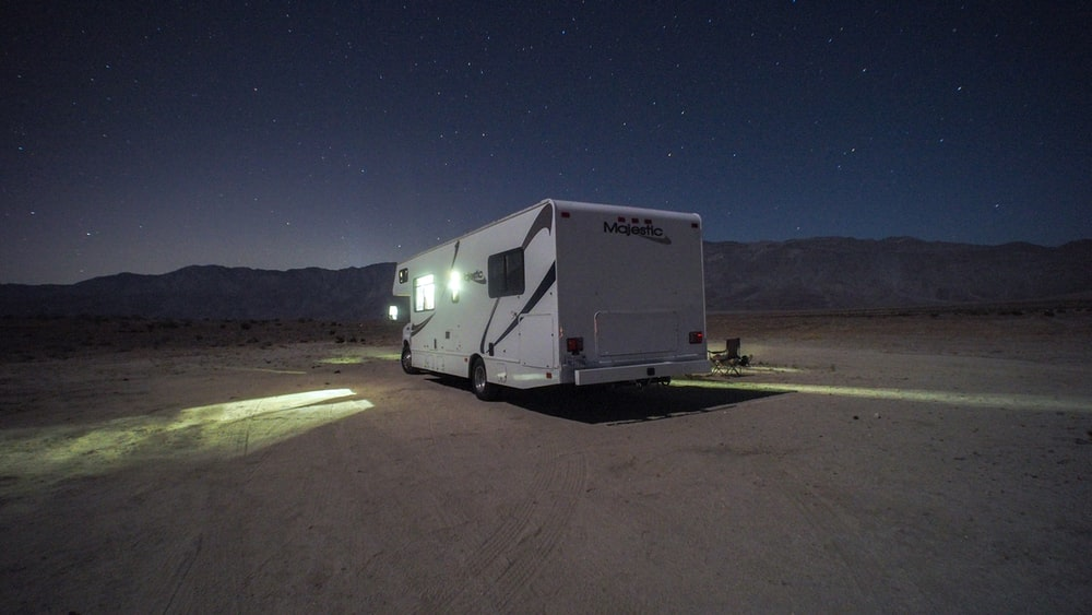 white and gray rv trailer on brown sand during night time