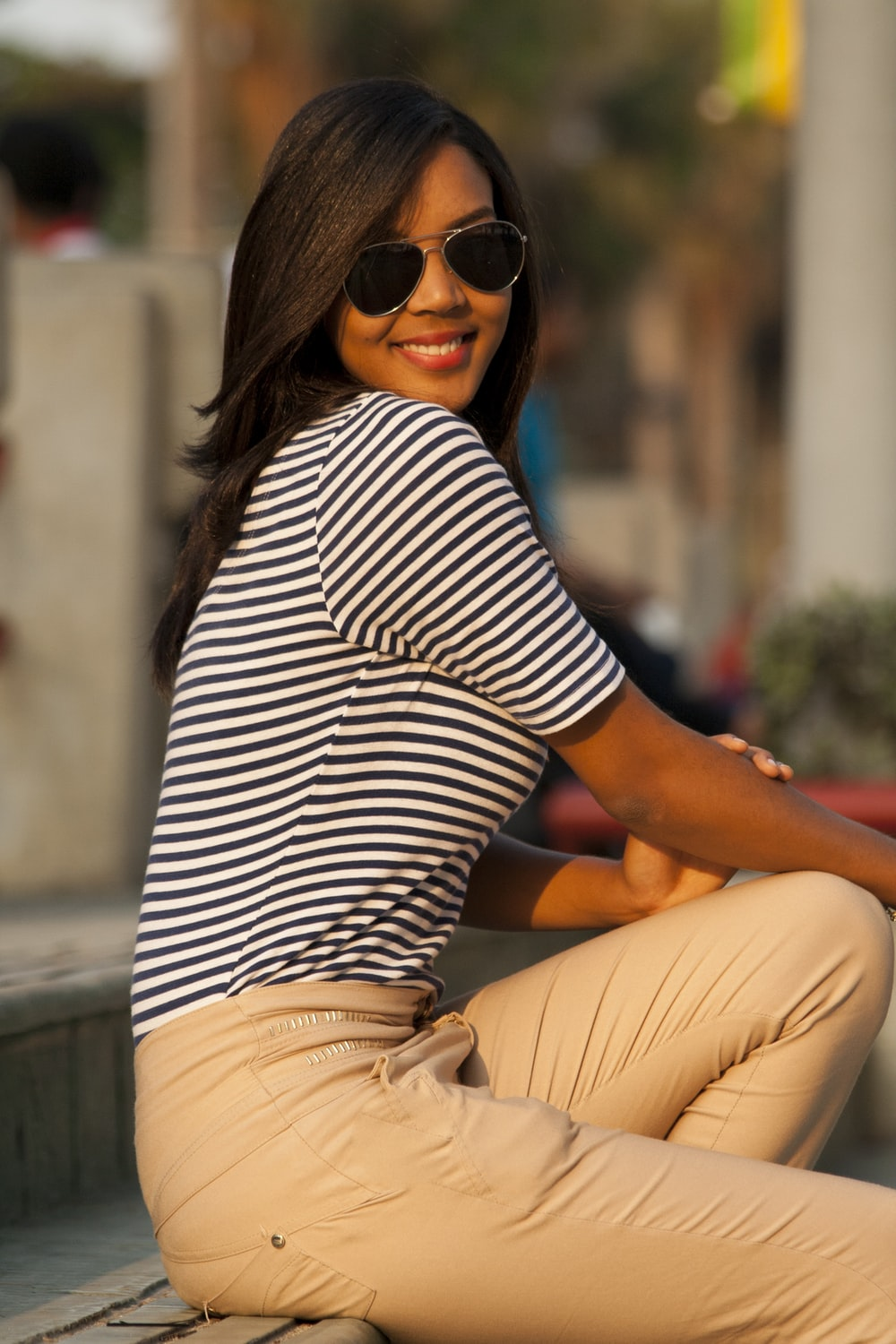 woman in black and white striped shirt and brown pants sitting on concrete bench during daytime