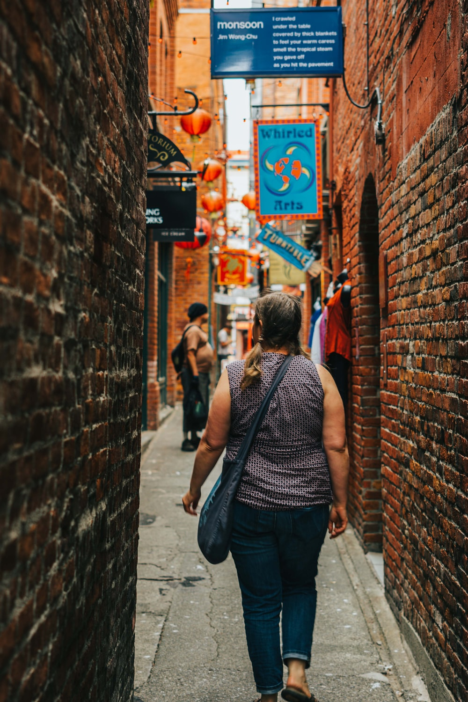 man in black tank top and blue denim jeans walking on sidewalk during daytime