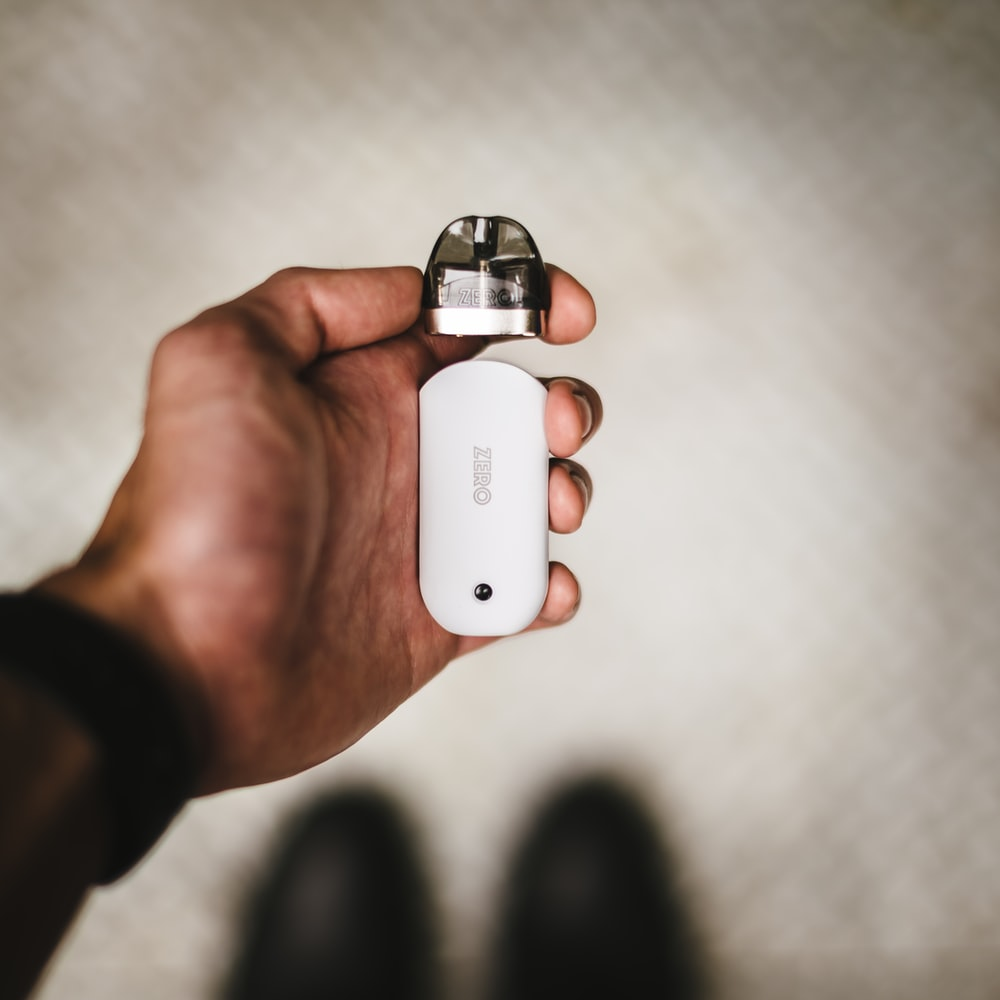 person holding white and silver bottle