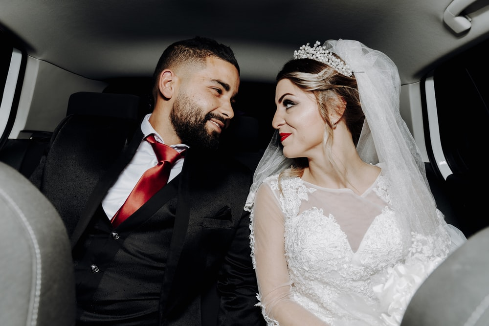 man in black suit jacket kissing woman in white wedding dress