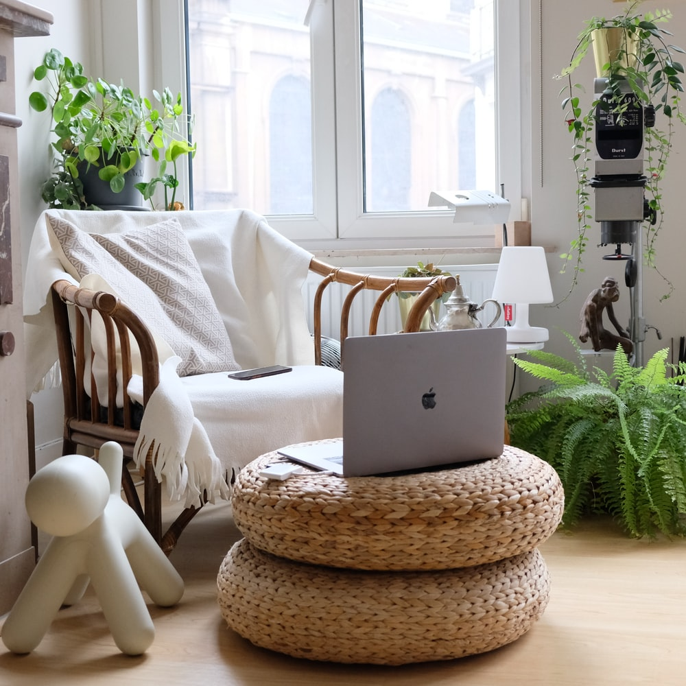silver macbook on brown woven round table