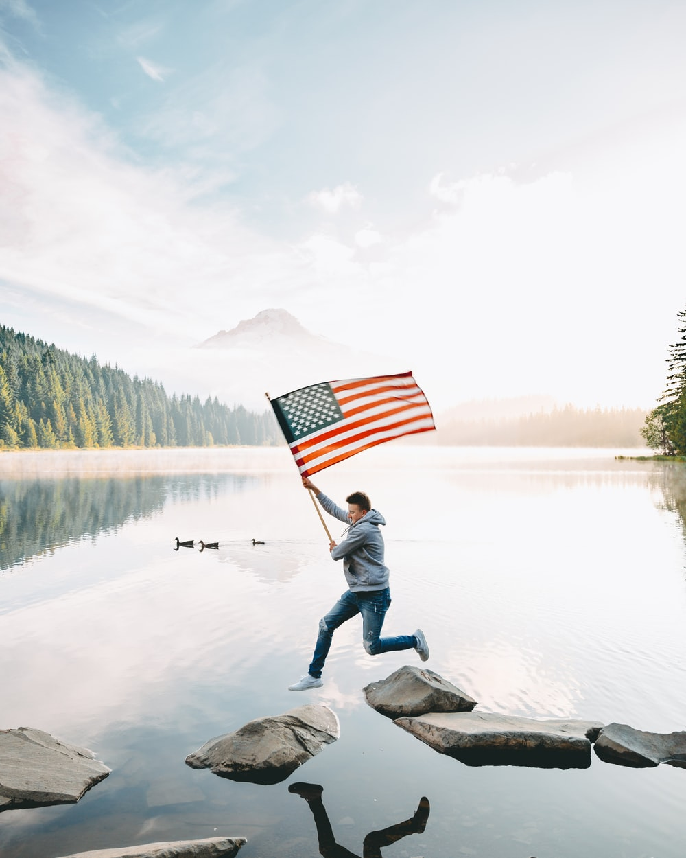 person holding us a flag standing on rock near lake during daytime