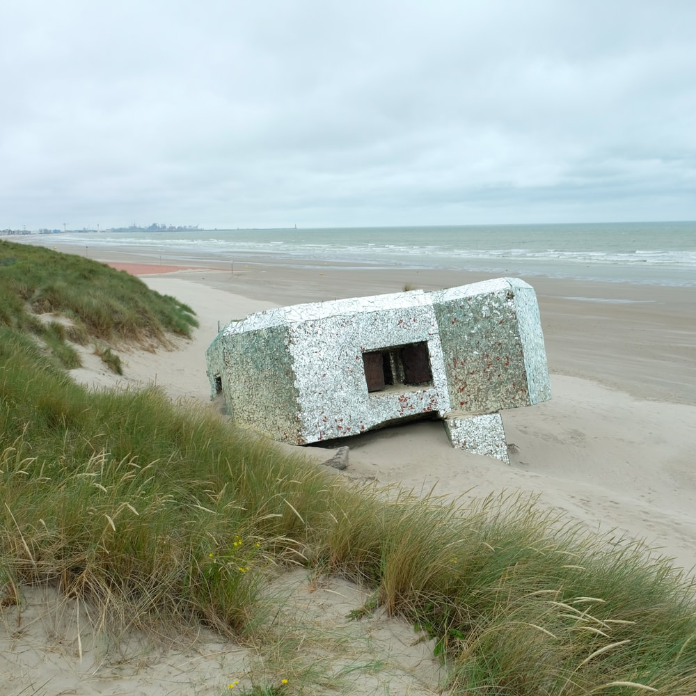 white and gray concrete house on seashore during daytime