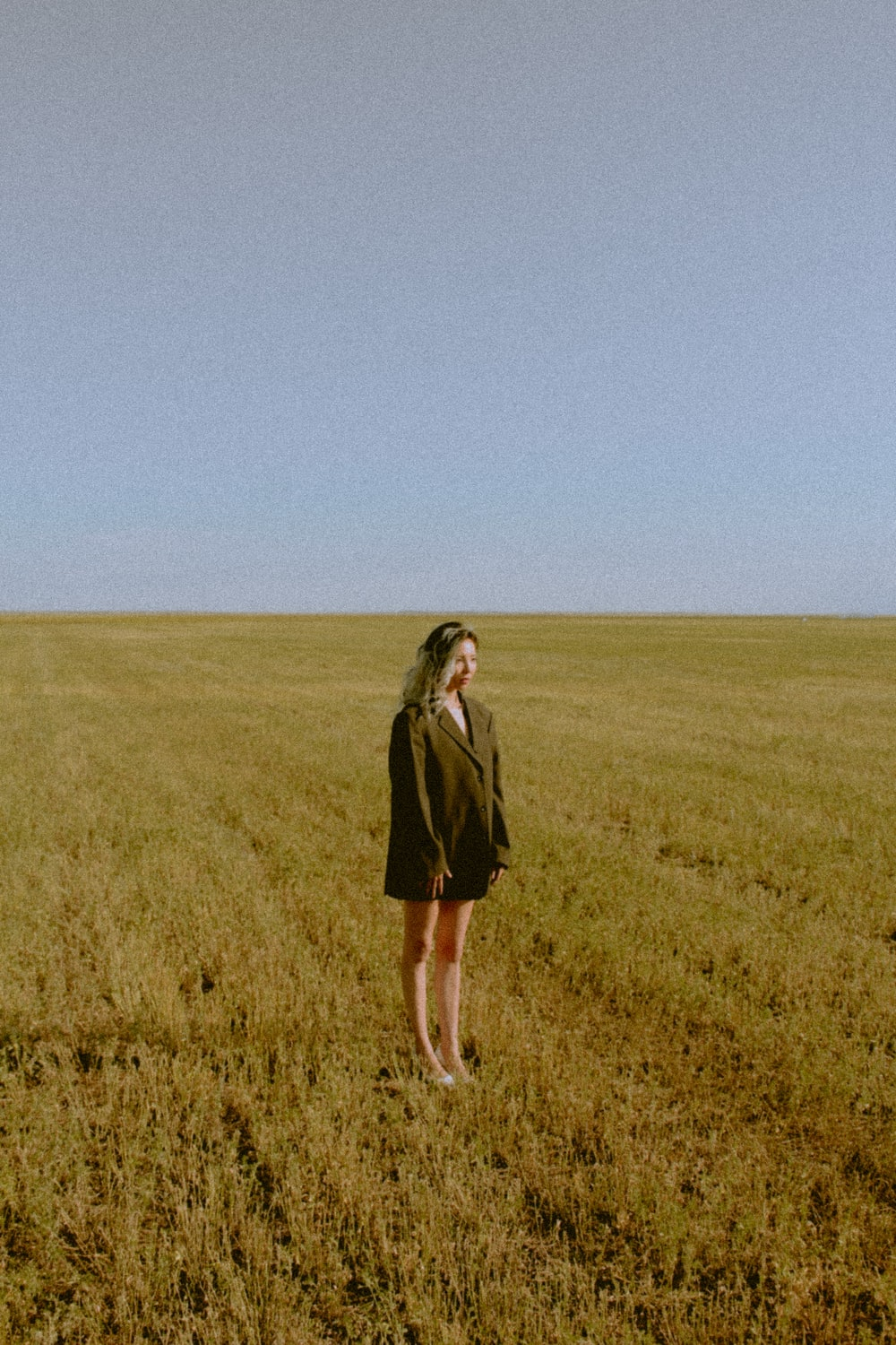 woman in black coat standing on green grass field during daytime