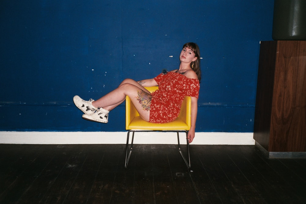 woman in red and white floral dress sitting on yellow chair