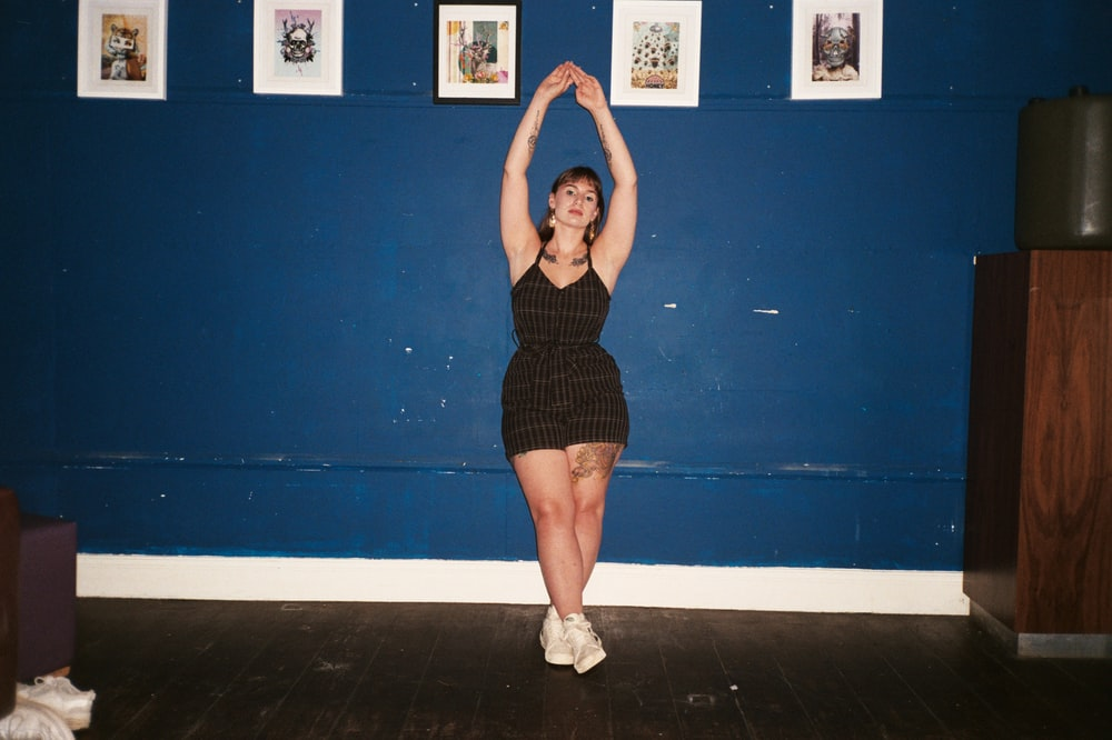 woman in black tank dress standing on blue wall