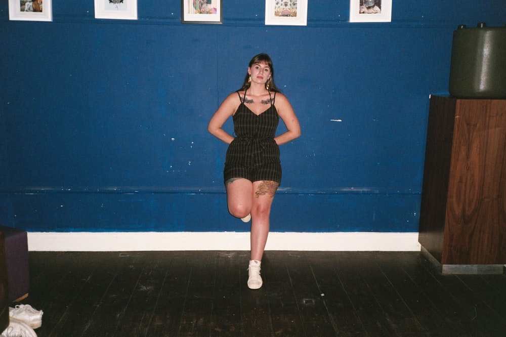 woman in black tank top and black shorts standing beside blue wall