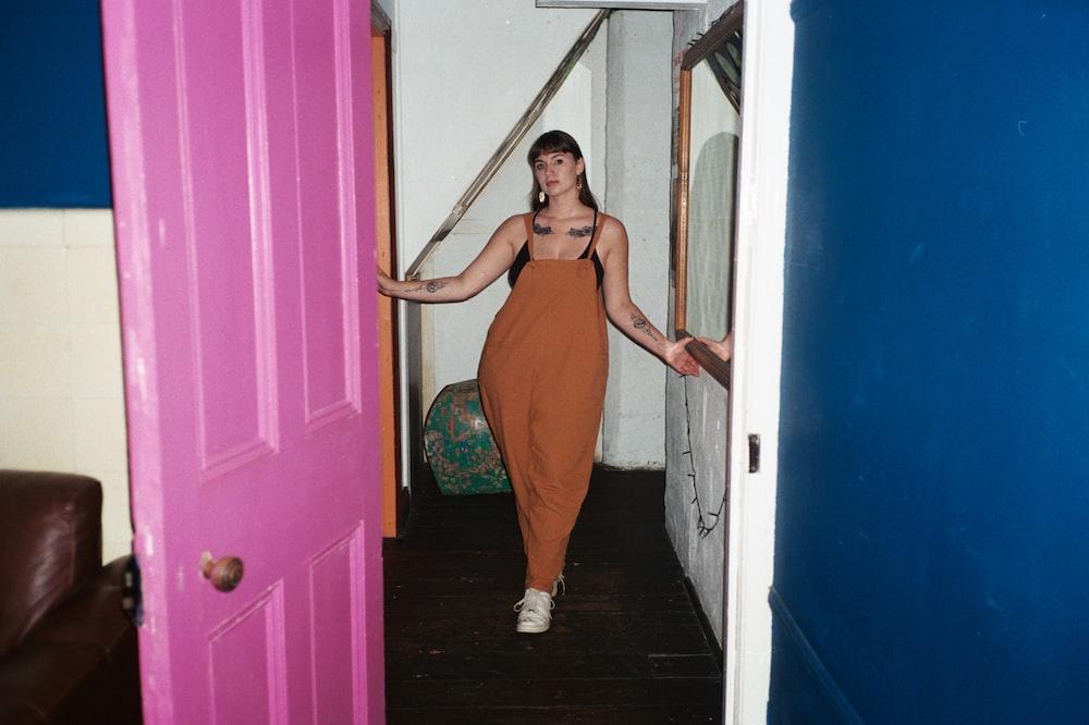 woman in orange dress standing near door