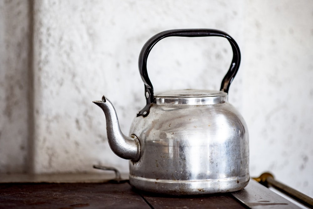stainless steel kettle on brown wooden table