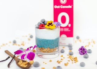 ice cream with purple flower on clear glass cup