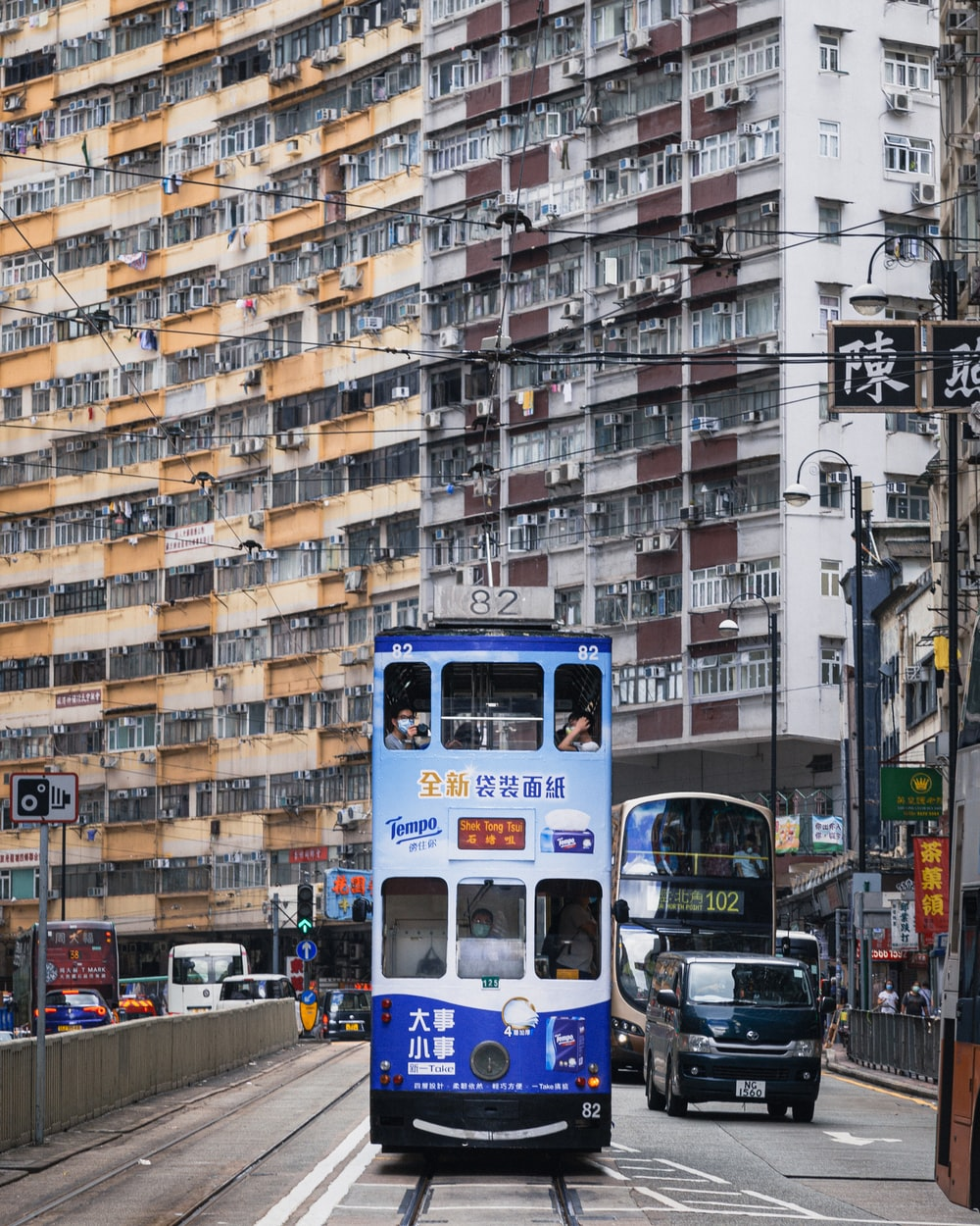 blue and white bus on road near high rise buildings during daytime
