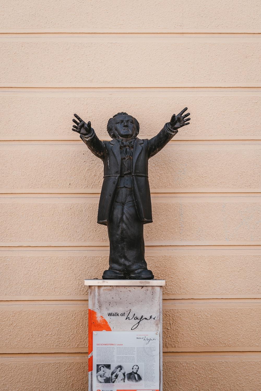 black statue of man on white concrete wall