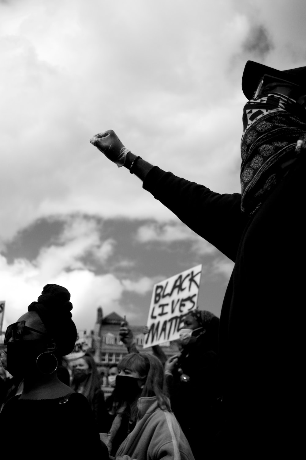 grayscale photo of person holding signage