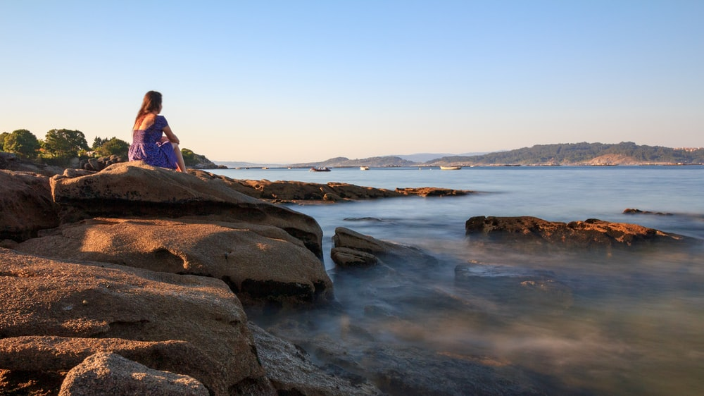 woman in pink jacket sitting on rock near body of water during daytime