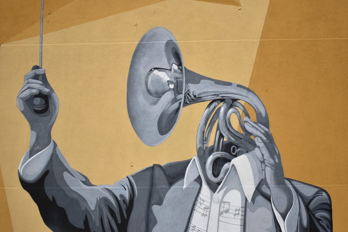 A grey scale conductor whose head is a trumbone against a mustard background with a diagonal shadow.
