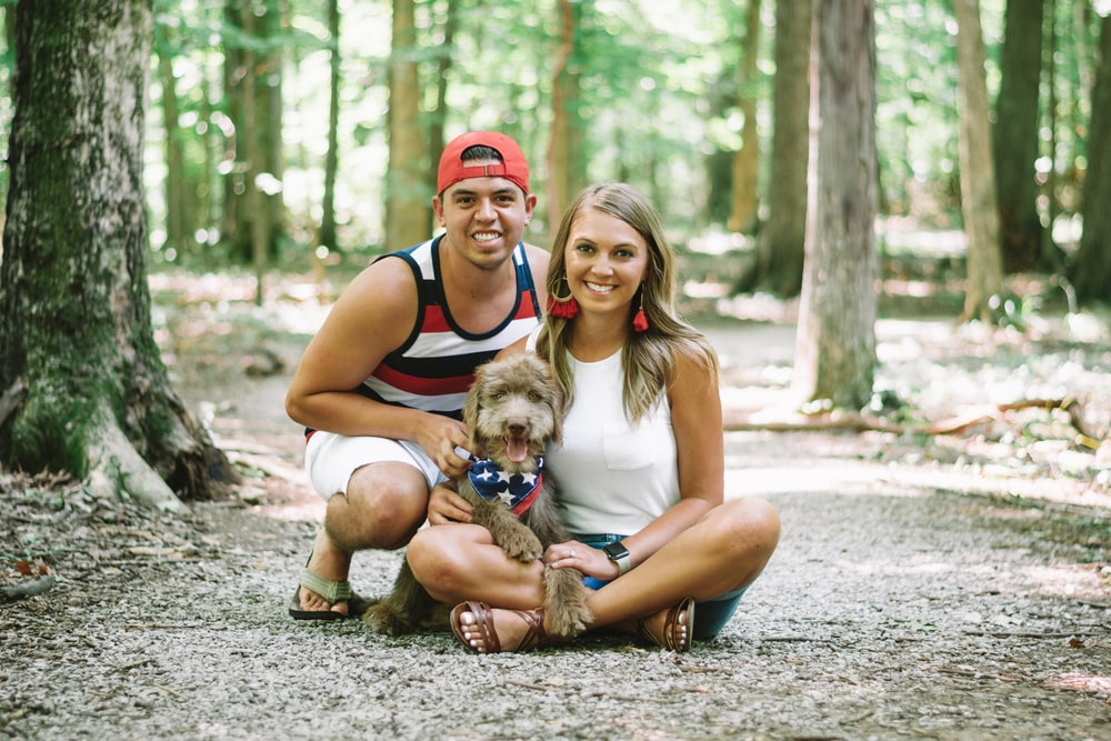 woman in red tank top sitting beside brown short coated puppy on gray concrete road during
