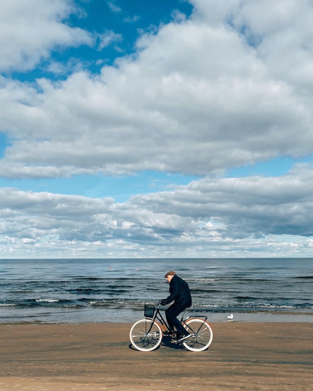 man in black jacket riding bicycle on beach during daytime