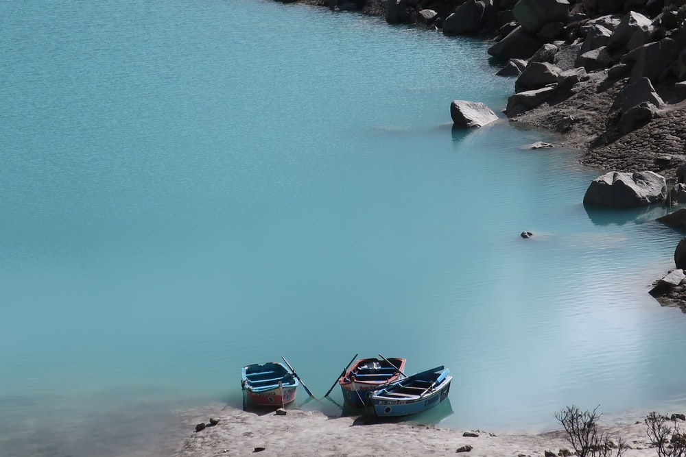 blue and red boat on body of water during daytime