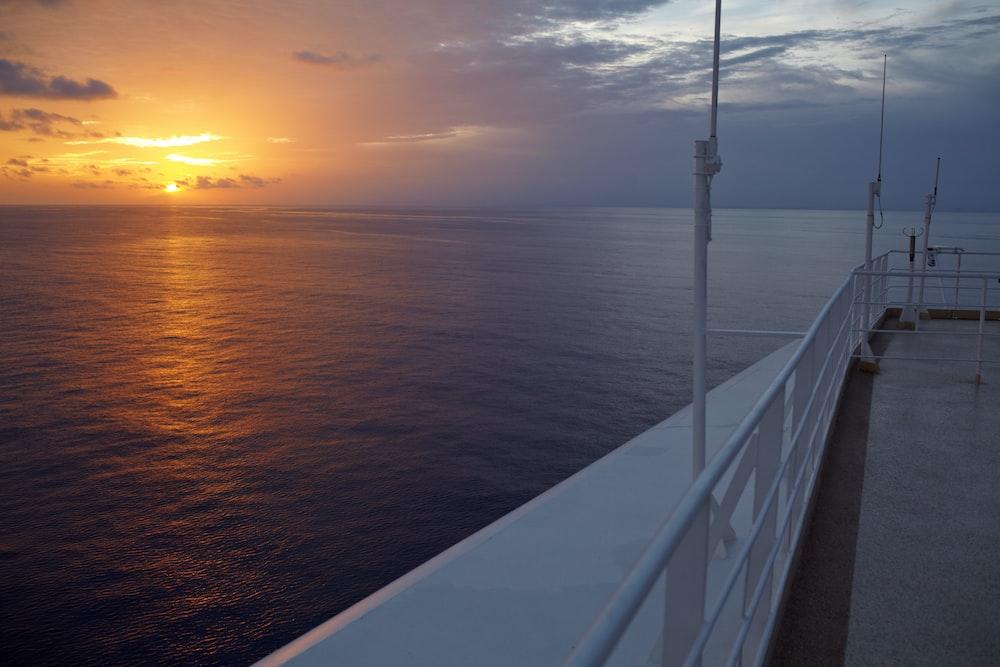 white metal railings near body of water during sunset