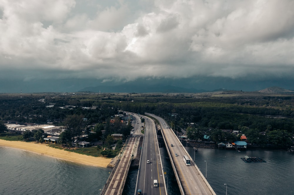 gray concrete road near body of water under white clouds during daytime