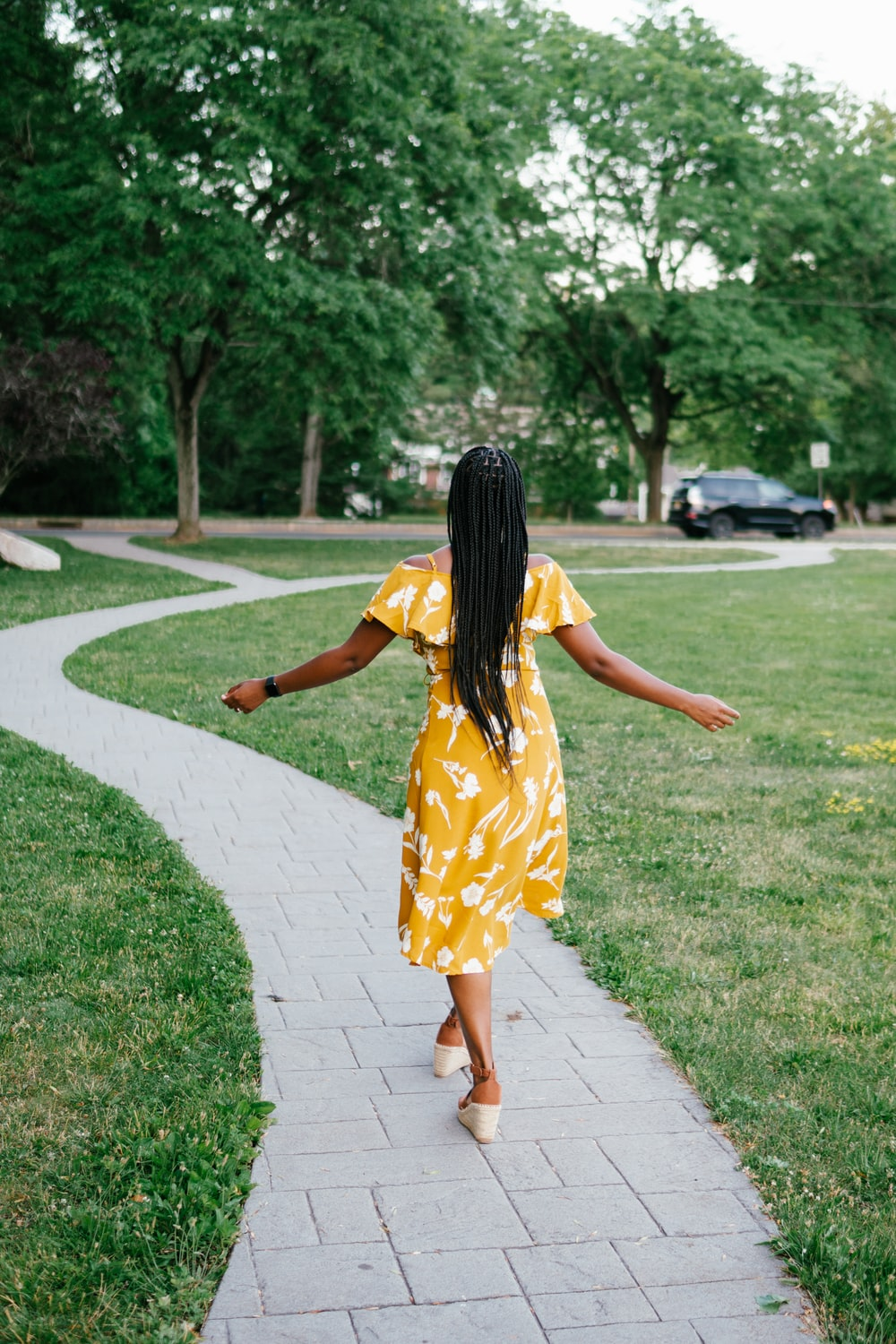 woman in yellow and white floral dress walking on pathway during daytime