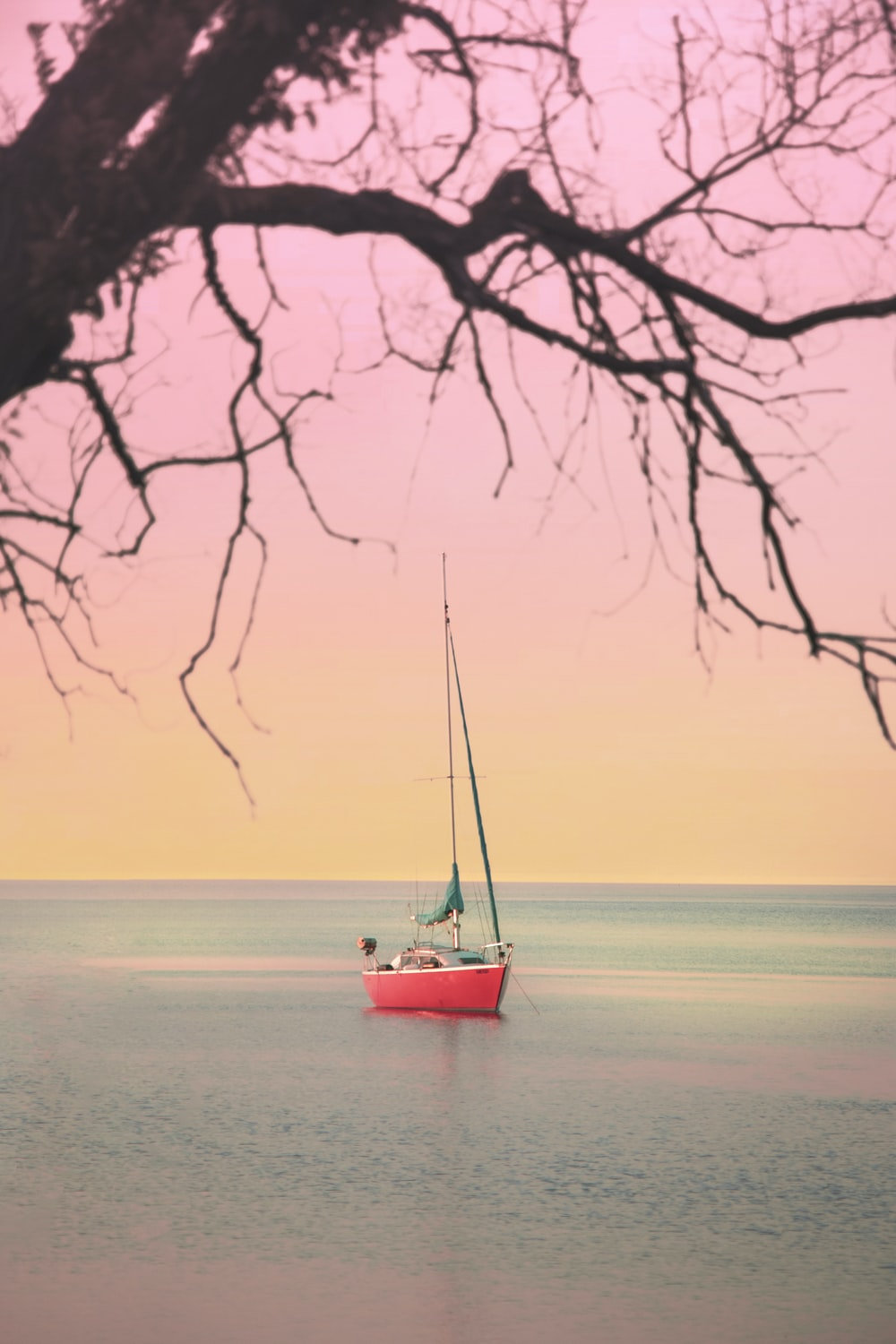 red boat on beach during sunset