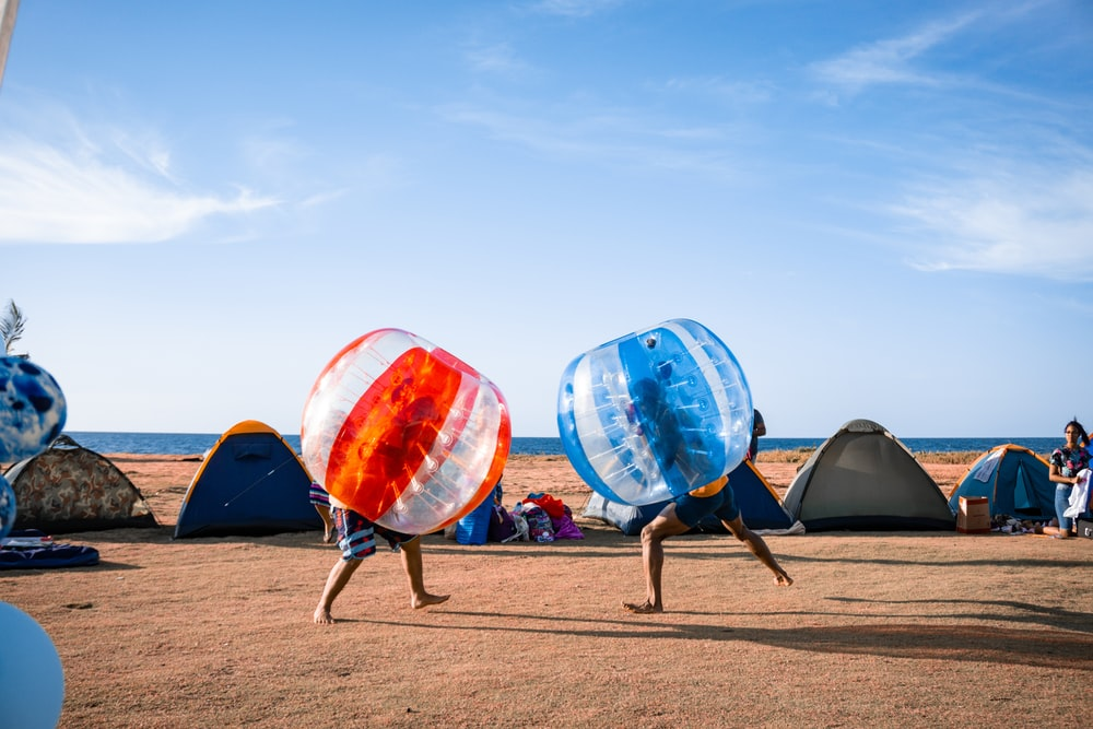 blue and orange outdoor umbrellas on brown sand during daytime
