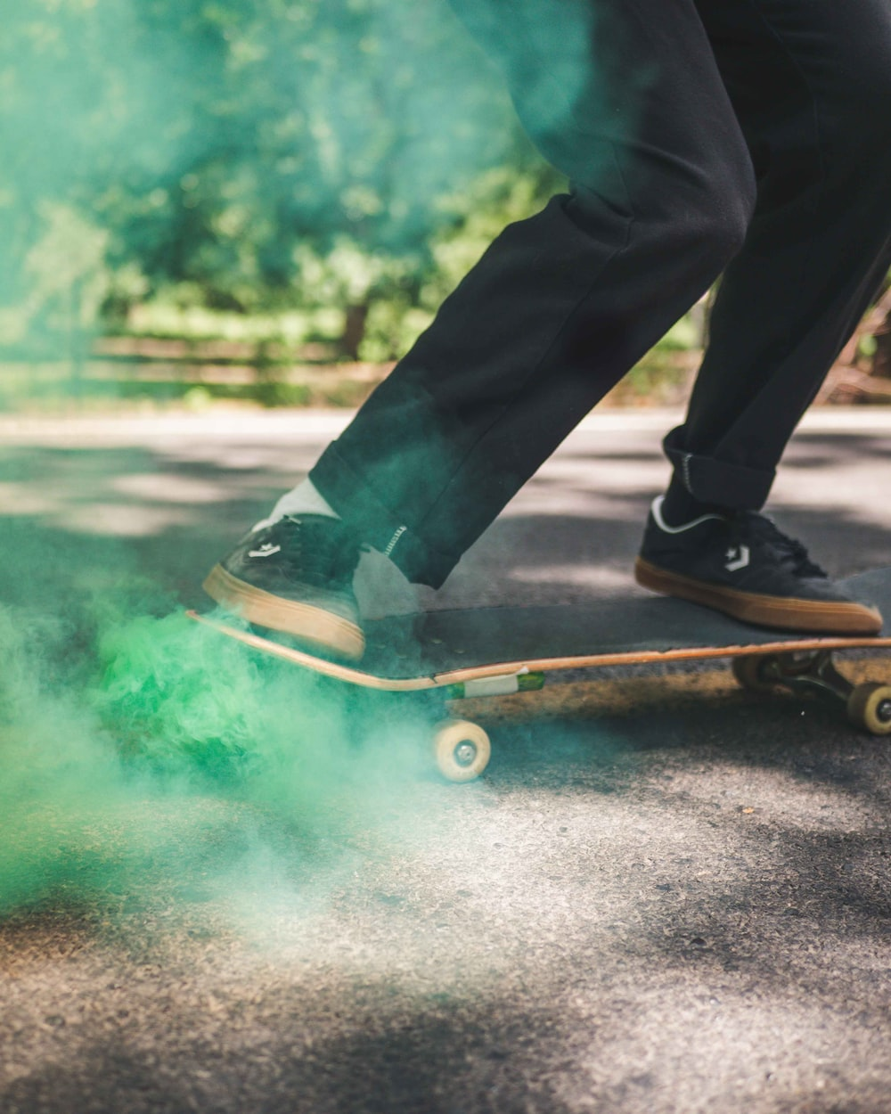 person in black pants and black shoes sitting on brown wooden skateboard