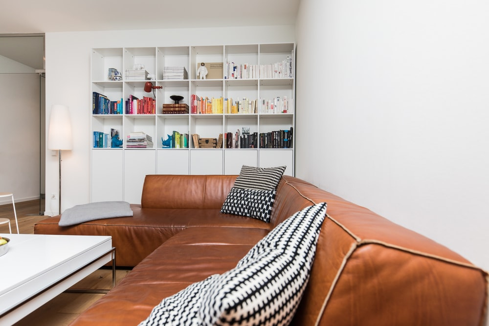 brown leather couch with throw pillows