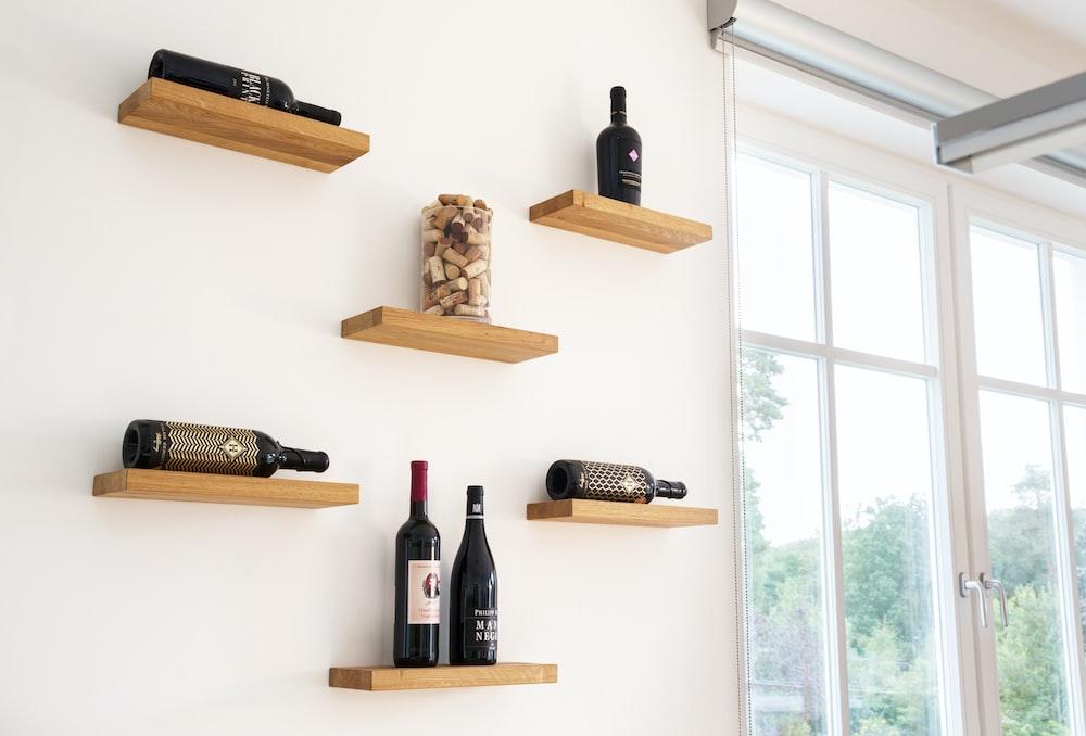 wine bottles on brown wooden wall rack